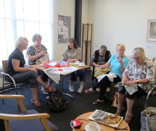 A group of the QVMAG Friends and others meeting over coffee and cake to create Welcome Home banners.